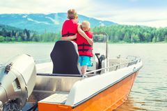 Two brothers swim on a motor boat on the lake. royalty free stock photo