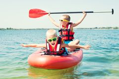 Two brothers swimming on stand up paddle board.Water sports , active lifestyle. Two brothers swimming on stand up paddle board.Water sports royalty free stock photos