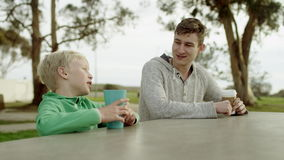Two brothers at the table outdoors. Young man and his little brother are sitting at the table outdoors and talking stock video