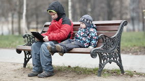Two brothers with tablet computer. Wide shot of young boy watching his brother as the two sit together on a wooden park bench in warm winter clothing with the stock video footage
