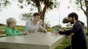 Two brothers and their friend at the table outdoors. Young man is drinking coffee while his friend is talking with his little brother while they all are sitting stock footage
