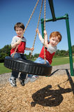 Two brothers on a tire swing. Two brothers have fun swinging on a tire swing at a neighborhood park Stock Photography