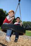 Two brothers on a tire swing royalty free stock images