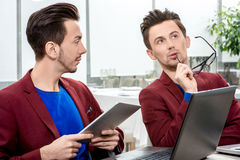 Two brothers twins working at the office Stock Image