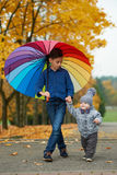 Two brothers under rainbow umbrella Stock Photography