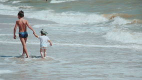 Two brothers walk along the beach in a sunny day. stock footage