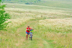Two brothers are walking on a bike. Outdoors Royalty Free Stock Image