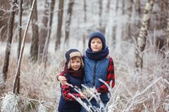 Two brothers on walr in winter forest. Best friends playing together Stock Images