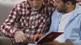 Two brothers watching family photos from album, remembering past times, close-up. Stock footage stock video