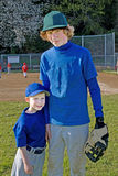 Two brothers wearing baseball uniforms. Stock Photography
