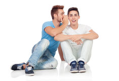 Two brothers whispering Stock Images