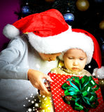 Two brothers who open a Christmas box of gifts on the new year Royalty Free Stock Images
