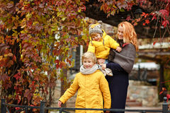 Two brothers in yellow jackets and mom are happy autumn leaves.  stock photo