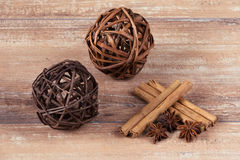 Two brown balls, star anise and cinnamon sticks on brown wooden board. Royalty Free Stock Photos