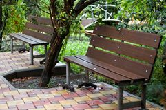 Free Two Brown Benches Standing On A Tile Of Yellow-red Color Royalty Free Stock Images - 108097739