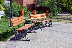 Two brown benches and an urn on the sidewalk in the park. On a sunny day Stock Photography