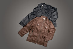 TWO BROWN AND BLACK KIDS LEATHER JACKET ON GRAY BACKGROUND Stock Photo