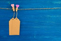Blank paper price tags or labels set and wooden pins decorated on hearts hanging on a rope on the blue wooden background. Stock Image