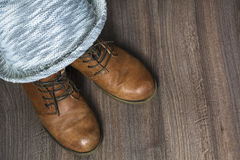 Two brown boots with grey hat. On the wooden background Royalty Free Stock Images