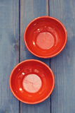 Two brown ceramic bowls on blue background. Two brown ceramic bowls on blue wooden background Stock Photos