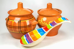 Two brown clay pots with colored ceramic spoon  on white background Royalty Free Stock Photos