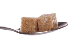 Two brown demerara sugar cube on a tea spoon Royalty Free Stock Photo
