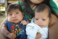 Two brown-eyed children  in Bolivia. Villa Alcira, Bolivia -circa June 2009: Mother holds her two children in her arms at Villa Alcira. Documentary editorial Stock Photos