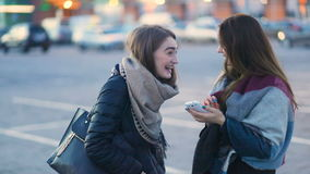 Two brown-haired fashionable attractive student girls with long hair talking, laughing and hugging on the parking stock footage