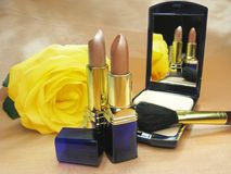 Two brown lipsticks powder and yellow rose Royalty Free Stock Images