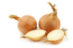 Two brown onions and a cut one Royalty Free Stock Images