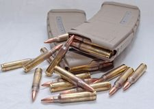 Two loaded . 223 rifle magazines with bullets laying around them royalty free stock image