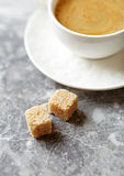 Two brown sugar cubes and a cup of coffee Royalty Free Stock Photos