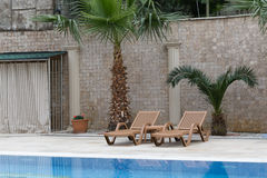 Two brown sunbeds by outdoor pool. Two brown sunbeds and two palm trees by outdoor pool agasint mosaic wall and columns Royalty Free Stock Images