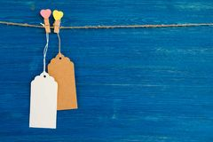 Blank paper price tags or labels set and wooden pins decorated on hearts hanging on a rope on the blue wooden background. Stock Images
