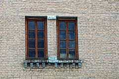 Two brown windows on a gray brick wall of a residential building Stock Image