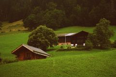 Two Brown Wooden Cabins in Green Grass Field Stock Images
