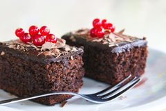 Two brownies with redberries on top, served in a plate on a wooden table. Two brownies with redberries on top, served in a white plate with silver fork on a Stock Image