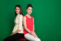 Two brunette girlfriends posing on green background Stock Photos