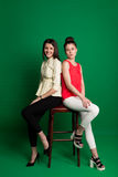 Two brunette girlfriends posing on green background Stock Images