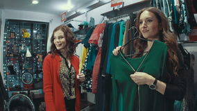 Two brunette girlfriends smiling and laughing choose the clothes in the store. Two brunette girlfriends smiling choose the clothes in the store, one of them stock footage