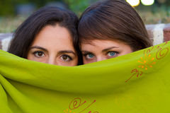 Two brunette girls behind a green scarf Royalty Free Stock Photo