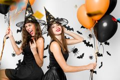 Two brunette girls in black dresses and witch hats have fun with balloons on the background of the wall with bats royalty free stock photo