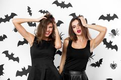 Two brunette girls dressed in black dresses grimace on the background of the wall with bats. Halloween party. royalty free stock images