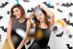 Two brunette girls wearing black dresses smile on the background of the wall with bats. Confetti around. Halloween royalty free stock image
