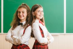 Two brunette schoolgirls in school red uniforms are standing in a classroom with books