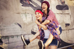 Two Brunette teenage girls friends in hipster outfit (jeans shorts, keds, plaid shirt, hat) with a skateboard at the park outdoors Royalty Free Stock Images