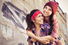 Two Brunette teenage girls friends in hipster outfit (jeans shorts, keds, plaid shirt, hat) with a skateboard at the park outdoors Stock Image
