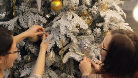 Two brunette woman in glasses fixed decorations on Christmas tree. On the white branches of a tree hanging shiny balls, snowflakes, stars and other glass toys stock video footage