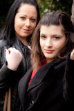 Two brunettes with black clothes. They have dark hair Royalty Free Stock Photography