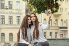 Two brunettes are curled in front of the smartphone. While they are making a selfie photo. They both have long brown hair that is long to the waist and they Royalty Free Stock Image